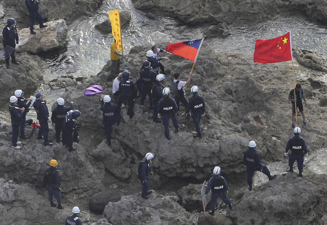 Activists holding Chinese and Taiwanese flags are arrested by Japanese police officers after landing on Uotsuri Island, one of the Diaoyu/Senkaku Islands, in the East China Sea, on August 15, 2012. (Photo by Yomiuri Shimbun/Masataka Morita/AP Photo)