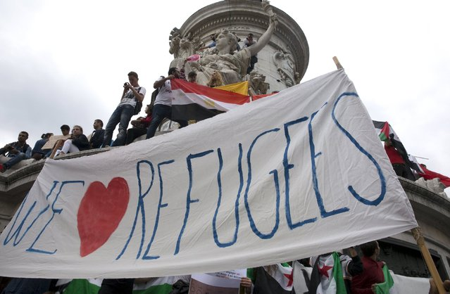 """People hold a banner that says """"We love refugees"""" as they take part in a demonstration asking for a change in the refugee policy in Europe on the Republique square in Paris, France, September 5, 2015. (Photo by Philippe Wojazer/Reuters)"""