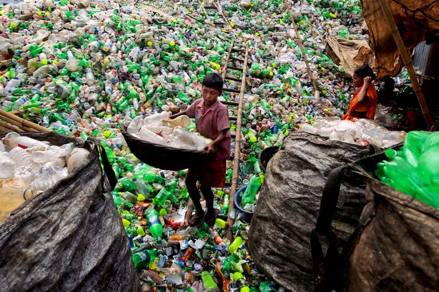 A Bangladeshi child laborer carries empty bottles at a plastic bottle recycling center in Dhaka, Bangladesh, on September 18, 2012. (Photo by A.M. Ahad/Associated Press)