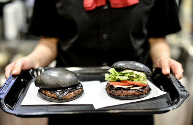 A Burger King employee holds two black hamburgers at a company restaurant on September 18, 2014 in Tokyo, Japan. (Photo by Keith Tsuji/Getty Images)