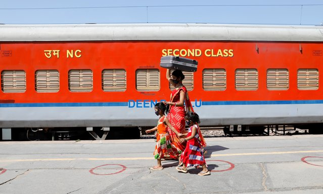 A migrant family walks to board train, after a limited reopening of India's giant rail network following a nearly seven-week lockdown to slow the spreading of the coronavirus disease (COVID-19), in Greater Noida, India, May 16, 2020. (Photo by Adnan Abidi/Reuters)