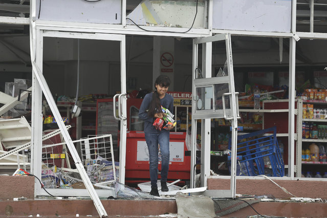 A woman takes goods from inside a destroyed convenience store trashed by Hurricane Odile in Los Cabos, Mexico, Monday, September 15, 2014. Hurricane Odile hammered Mexico's Baja California Peninsula overnight, tearing away the facades of luxury resorts, shattering countless car and hotel windows and leaving lobbies swamped and full of debris on Monday. (Photo by Victor R. Caivano/AP Photo)