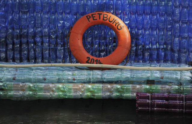A safety ring is seen on a boat, made with plastic bottles, in Nymburk, Czech Republic July 12, 2014. Jan Kara, a 22-year-old student, and Jakub Bures, a 22-year-old car mechanic, built the 10-metre (32.8-feet) long boat from 5000 plastic bottles strapped to a wooden frame. They and two other men plan to pedal from their hometown Nymburk down the river Elbe to Hamburg in Germany to draw attention to an increasing plastic pollution in Europe, they said. (Photo by Rene Volfik/Reuters)