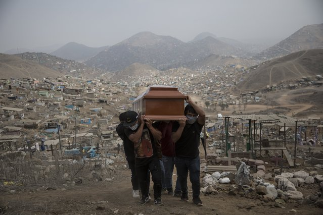 Relatives carry the coffin of a suspected COVID-19 victim at the Nueva Esperanza cemetery on the outskirts of Lima, Peru, Thursday, May 28, 2020. (Photo by Rodrigo Abd/AP Photo)