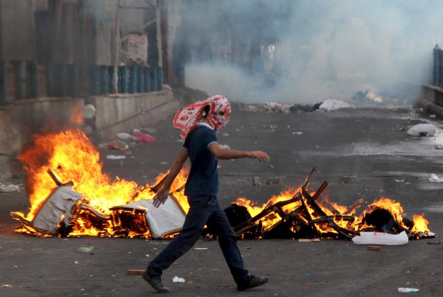 A masked protester walks past burning chairs as they clash with riot police in the Kurdish dominated southeastern city of Diyarbakir, Turkey, September 13, 2015. (Photo by Sertac Kayar/Reuters)