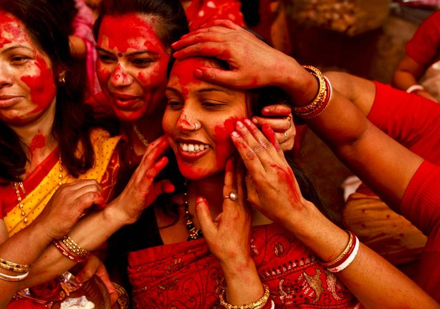 Women apply vermillion powder on each other during Durga Puja festivities in New Delhi, India October 24, 2012. The festival commemorates the slaying of a demon king by lion-riding, ten armed goddess Durga, marking the triumph of good over evil. (Photo by Rajesh Kumar Singh/Associated Press)