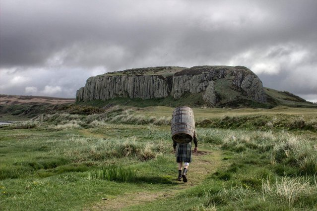 Davy Ballantyne, 59, walks around the Isle of Arran carrying a 50kg whiskey barrel, supporting Samaritans Emergency Appeal, a mental health charity, in the Isle of Arran, Scotland on May 26, 2020. (Photo by Fraser Aitchison/Big Davy's Challenges via Reuters)