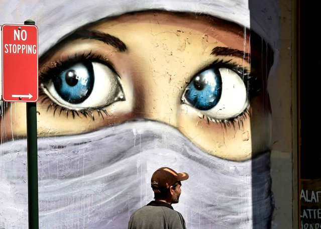 People walk past a mural of a Muslim woman painted on a wall in an inner city suburb in Sydney on October 2, 2014. Australian military jets are to join in the US-led air war against the Islamic State group in Iraq, conducting refuelling and support missions, Prime Minister Tony Abbott said. (Photo by Peter Parks/AFP Photo)