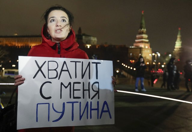 """In this file photo taken on Wednesday, March 11, 2020, A protester holds a poster that reads: """"Enough Putin for me"""", in front of the monument of the Prince Vladimir next to the Kremlin in Moscow. The constitutional reform passed by the Duma on Wednesday would allow Putin to run for presidency two more times after 2024. Before the national vote, it will be reviewed by Russia's Constitutional Court. (Photo by Pavel Golovkin/AP Photo/File)"""