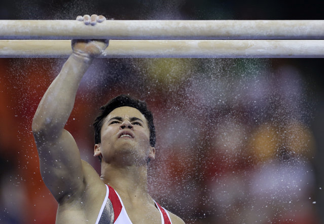 Switzerland's Eddy Yusof puts powder on the bars as he prepares to compete on the parallel bars during the Artistic Gymnastics World Championship at the Guangxi Gymnasium in Nanning, capital of southwest China's Guangxi Zhuang Autonomous Region Saturday, October 4, 2014. (Photo by Andy Wong/AP Photo)