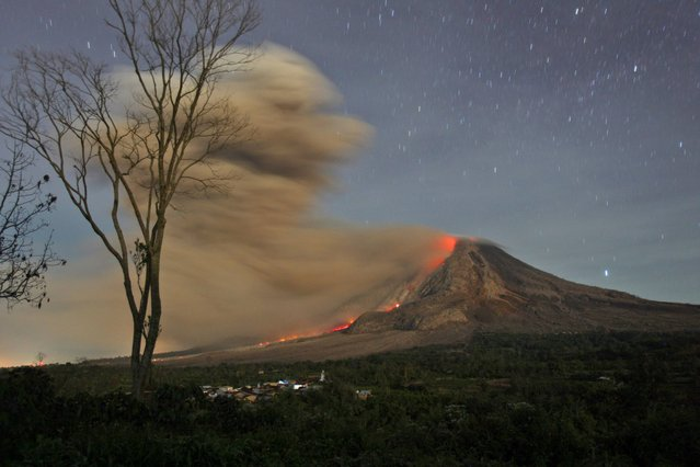 In this photo made with a slow shutter speed, Mount Sinabung spews hot lava and volcanic ash as seen from Jeraya, North Sumatra, Indonesia, early Tuesday, October 14, 2014.  Mount Sinabung, among about 130 active volcanoes in Indonesia, has sporadically erupted since 2010 after being dormant for 400 years. (Photo by Binsar Bakkara/AP Photo)