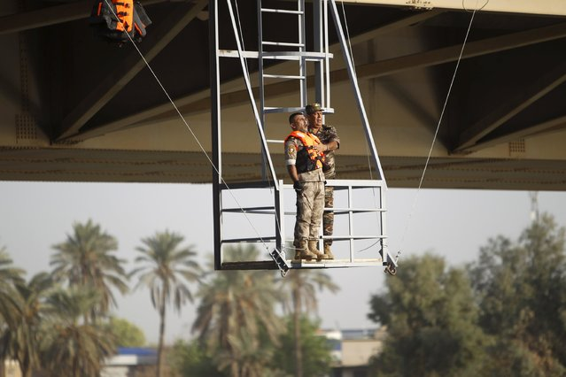 "An Iraqi army cadet gets ready to perform ""the leap of faith"" from a bridge in Baghdad, September 22, 2015. (Photo by Ahmed Saad/Reuters)"