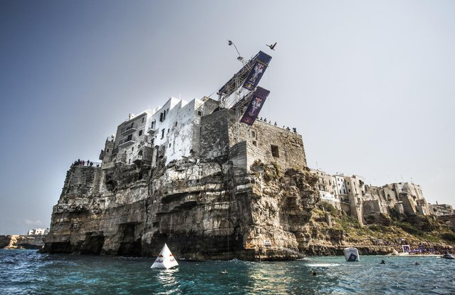 In this handout image provided by Red Bull, Kris Kolanus of Poland dives from the 27 metre platform during the fifth stop of the Red Bull Cliff Diving World Series, Polignano a Mare, Italy. (Photo by Dean Treml/ANSA/Red Bull Press Office)