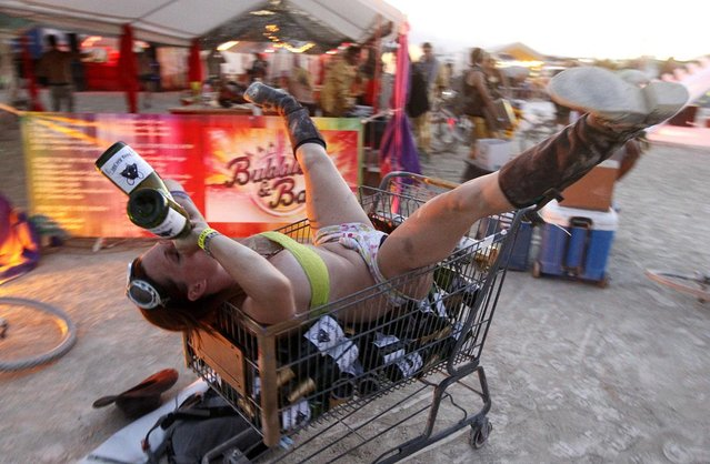 """A participant who goes by the playa name """"Honey B"""" drinks from bottles of champagne as she lies atop empty bottles in a shopping cart during the """"Gold Bikini Happy Hour"""" hosted by Rat Camp at the 2013 Burning Man arts and music festival in the Black Rock desert of Nevada, August 30, 2013. (Photo by Jim Bourg/Reuters)"""
