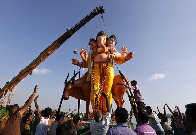 Devotees raise their arms as they carry an idol of the Hindu god Ganesh, the deity of prosperity, on a crane for immersion into the Sabarmati river on the last day of the 10-day-long Ganesh Chaturthi festival in Ahmedabad, India, September 27, 2015. (Photo by Amit Dave/Reuters)