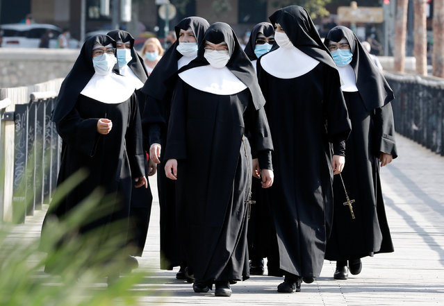Several nuns wearing face masks walk along a street in Valencia, eastern Spain, 29 July 2020. Local police strengthen controls as the mask use is compulsory in public spaces. (Photo by Juan Carlos Cardenas/EPA/EFE)