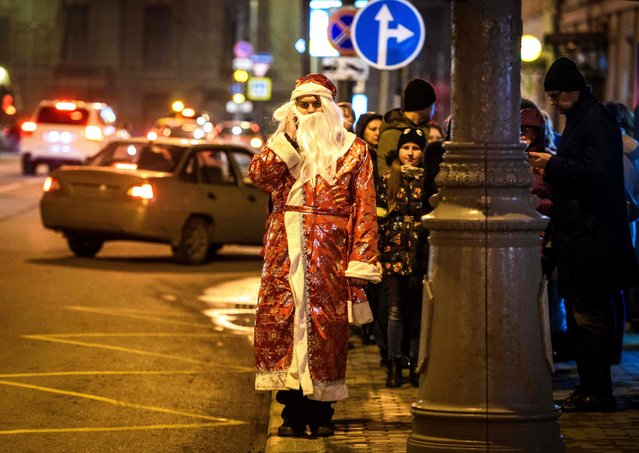 An impersonator of Santa Claus talks on his phone while waiting on a bus station in central Moscow on December 17, 2017. (Photo by Mladen Antonov/AFP Photo)