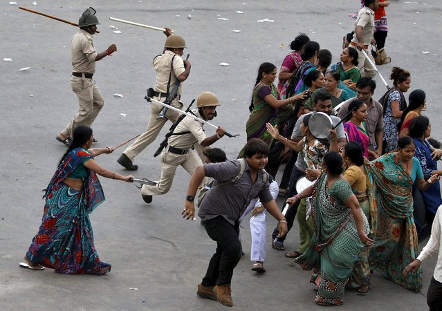 Indian policemen use batons to disperse the members of the Patel community during a protest rally in Ahmedabad, India, September 19, 2015. (Photo by Amit Dave/Reuters)