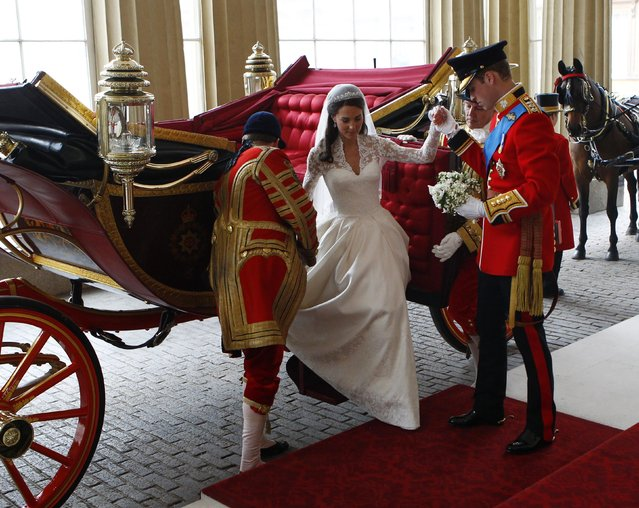 Prince William (R) helps his wife Catherine, Duchess of Cambridge, to leave the 1902 State Landau carriage as they arrive at Buckingham Palace after their wedding in Westminster Abbey in central London April 29, 2011. (Photo by Andrew Winning/Reuters)