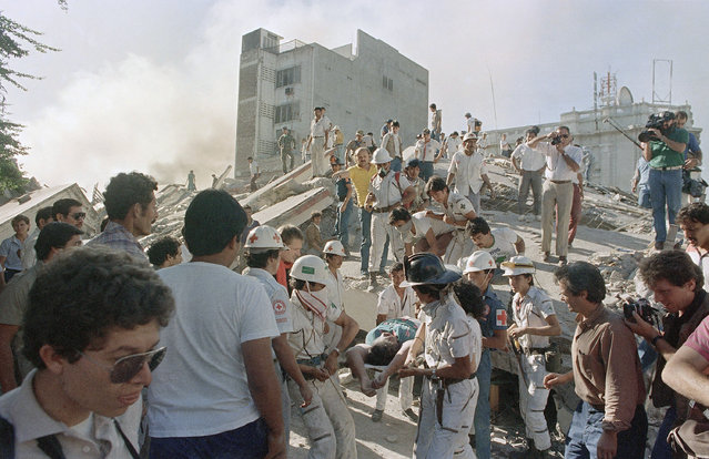 Rescue workers carry the body of an unidentified woman from the rubble of the Ruben Diaro Building after the building collapsed in an earthquake, October 1986, San Salvador, El Salvador. The tremor left more than 1,000 persons dead and thousands homeless. (Photo by Joe Skipper/AP Photo)