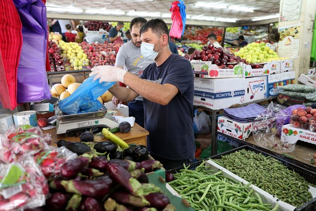A Palestinian man a vendor wears a protective face mask while selling fruit and vegetables on a market ahead of Eid al-Adha in the West Bank city of Hebron, 30 July 2020. Eid al-Adha is the holiest of the two Muslims holidays celebrated each year, it marks the yearly Muslim pilgrimage (Hajj) to visit Mecca, the holiest place in Islam. Muslims slaughter a sacrificial animal and split the meat into three parts, one for the family, one for friends and relatives, and one for the poor and needy. (Photo by Abed Al Hashlamoun/EPA/EFE)