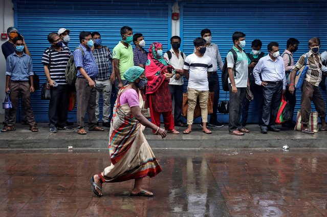 Passengers wearing masks wait in a queue to board a bus, after authorities eased lockdown restrictions that were imposed to slow the spread of the coronavirus disease (COVID-19), in Kolkata, August 6, 2020. (Photo by Rupak De Chowdhuri/Reuters)