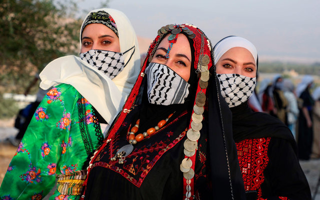 Palestinian women wearing protective masks amid the COVID-19 pandemic pose in their traditional attire during an event to celebrate the Palestinian Traditional Dress Day and protest Israel's plan to annex parts of the occupied West Bank, in the village of Al-Jiftlik in the Jordan Valley region, on July 26, 2020. (Photo by Jaafar Ashtiyeh/AFP Photo)