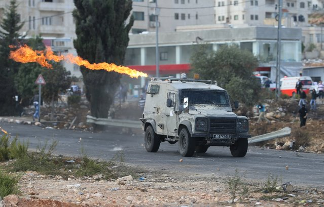 A Molotov cocktail is thrown by Palestinians at an Israeli army jeep during clashes near the Jewish settlement of Bet El, near the West Bank city of Ramallah October 8, 2015. (Photo by Mohamad Torokman/Reuters)