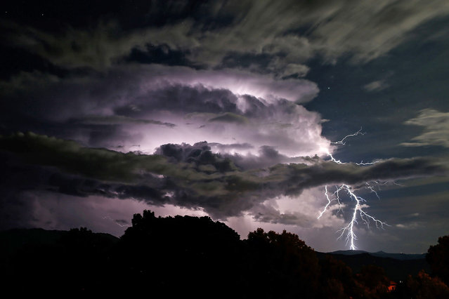 A picture taken on September 10, 2019 shows a light storm over the Taravo Valley in Cognocoli-Monticchi, on the French Mediterranean island of Corsica. (Photo by Pascal Pochard-Casabianca/AFP Photo)