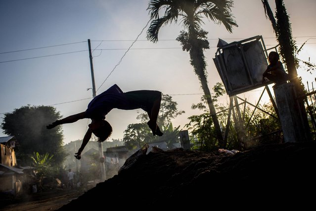 A boy does a backflip off a mound of dirt on November 6, 2014 in San Antonio, Samar, Philippines. Residents of Leyte and surrounding districts are preparing for the 1-year anniversary since Super Typhoon Yolanda struck the coast on November 8, 2013, leaving more than 6000 dead and many more homeless. (Photo by Chris McGrath/Getty Images)