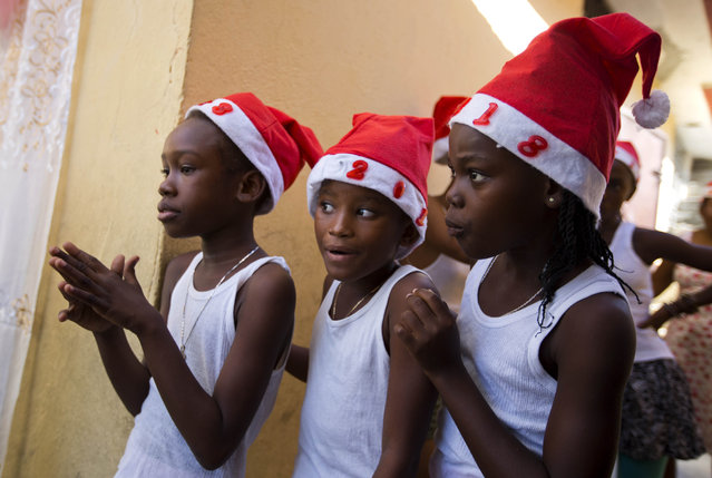 Girls wait back stage while they participate in a Christmas event in Port-au-Prince, Haiti, Friday December 22, 2017. (Photo by Dieu Nalio Chery/AP Photo)