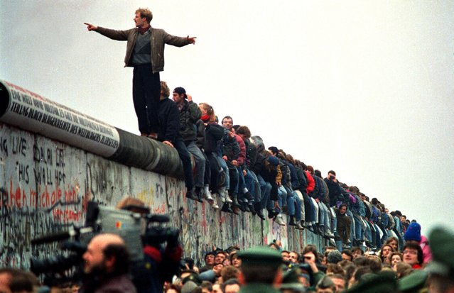 People stand on a section of the Berlin Wall at Potsdamer Platz on November 11, 1989. (Photo by John Tlumacki/Getty Images)