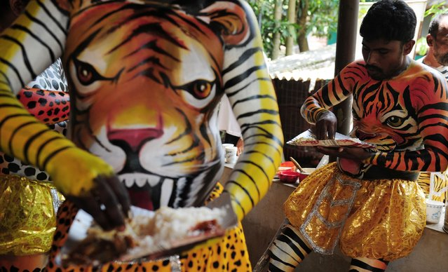 """Indian performers wearing body-paint depicting tigers eat lunch as they wait for the artwork to dry as they prepare to take part in the """"Pulikali"""", or Tiger Dance, in Thrissur on September 17, 2016. (Photo by Arun Sankar/AFP Photo)"""
