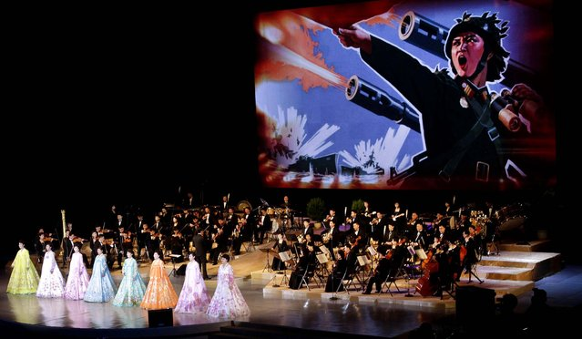 An image depicting a female North Korean soldier leading an artillery attack is projected on a large screen behind singers and the Unhasu Orchestra during a concert to mark International Women's Day in Pyongyang, North Korea. (Photo by Jon Chol Jin/Associated Press)