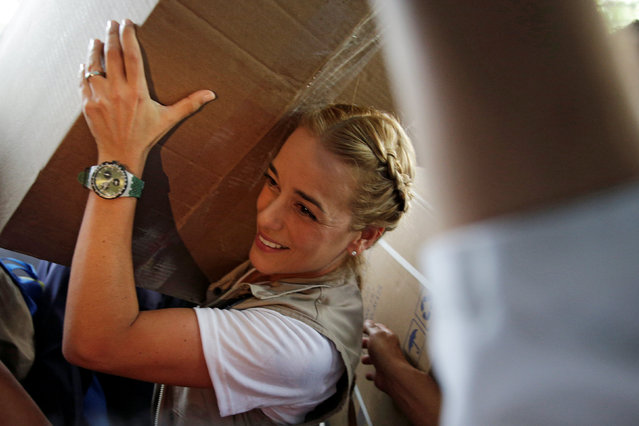 """Lilian Tintori, wife of jailed Venezuelan opposition leader Leopoldo Lopez, carries a box during a gathering to donate supplies at the """"J.M. de los Rios"""" Children Hospital in Caracas, Venezuela September 27, 2016. (Photo by Marco Bello/Reuters)"""