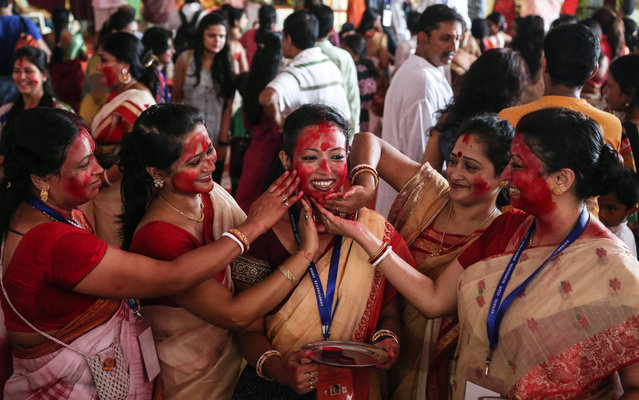 Women devotees of the Bengali community apply Sindoor or vermillion on each other's faces as they take part in the 'Sindoor Puja', a ritual before the immersion of Goddess Durga idols into water bodies on the last day of the Durga Puja Festival in Mumbai, India, 22 October 2015. Sindoor puja marks the end of Durga Puja Festival. (Photo by Divyakant Solanki/EPA)