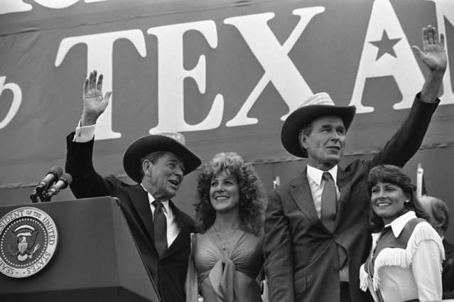 President Ronald Reagan, left, and Vice President George H.  Bush don western-style straw hats presented to them by two cheerleaders at an outdoor political rally on Wednesday, July 25, 1984 in Austin, Texas.   Houston Oilers cheerleader Cathy Ludwig, with Reagan, and University of Texas cheerleader Leslie Scott, with Bush, made the presentation. (Photo by AP Photo)