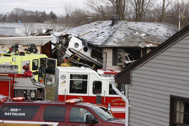 The front end of a Hawker Beachcraft Premier jet sits in a room of a home on Iowa Street in South Bend, Ind., Sunday, March 17, 2013. Authorities say a private jet apparently experiencing mechanical trouble crashed resulting in injuries. Federal Aviation Administration spokesman Roland Herwig says the Beechcraft Premier I twin-jet had left Tulsa, Okla.'s Riverside Airport and crashed near the South Bend Regional Airport on Sunday afternoon. (Photo by Mike Hartman/AP Photo/South Bend Tribune)