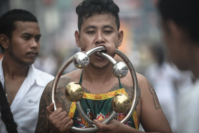 A devotee of the Nine Emperor Gods parades through the town of Phuket with giant metal rings through his cheeks during the annual Phuket Vegetarian Festival in the southern province of Phuket on October 3, 2016. (Photo by Lillian Suwanrumpha/AFP Photo)