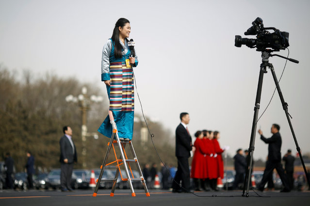 A journalist reports on a ladder outside the Great Hall of the People during the opening session of the National People's Congress (NPC) in Beijing, China March 5, 2018. (Photo by Thomas Peter/Reuters)