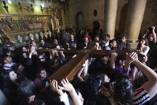 Worshippers carry a cross in the Church of the Holy Sepulchre on Good Friday during Holy Week, in Jerusalem's Old City March 29, 2013. Christian worshippers retraced the route Jesus took along Via Dolorosa to his crucifixion in the Church of the Holy Sepulchre. Holy Week is celebrated in many Christian traditions during the week before Easter. (Photo by Nir Elias/Reuters)