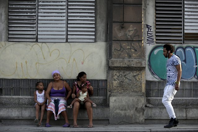 A man walks past two women as they sit with their daughters on a sidewalk in Havana October 26, 2015. (Photo by Enrique De La Osa/Reuters)