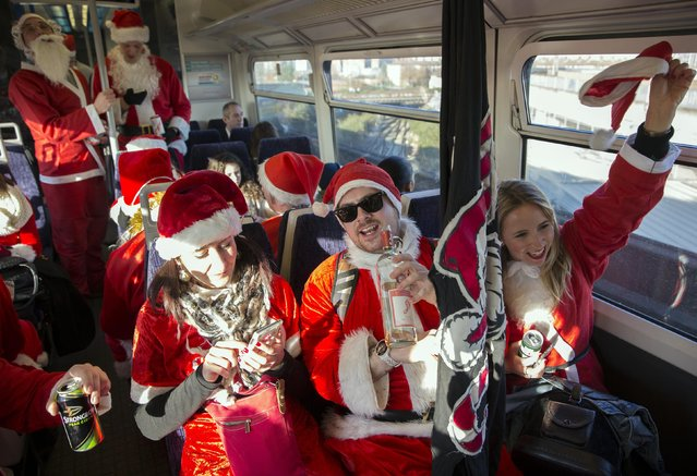 Participants dressed in Santa costumes sing on a train during the annual SantaCon event in London December 6, 2014. (Photo by Neil Hall/Reuters)
