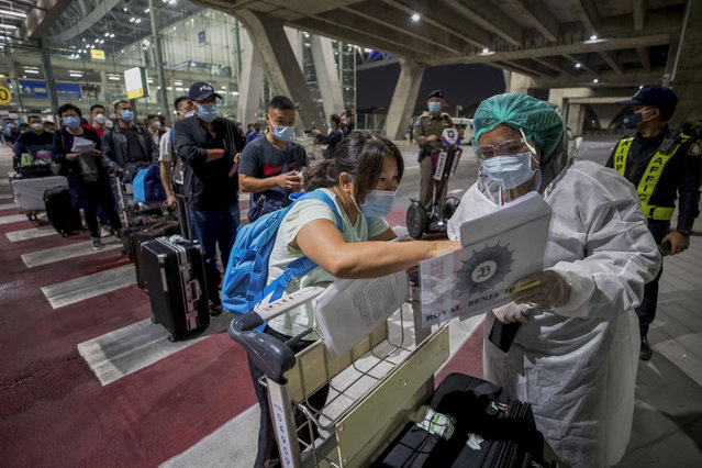 A public health worker screens Chinese tourists from Shanghai who arrived at Suvarnabhumi airport on a Special Tourist Visa, in Bangkok, Thailand, Tuesday, October 20, 2020. Thailand on Tuesday took a modest step toward reviving its coronavirus-battered tourist industry by welcoming 39 visitors who flew in from Shanghai, the first such arrival since normal traveler arrivals were banned almost seven months ago. (Photo by Wason Wanichakorn/AP Photo)