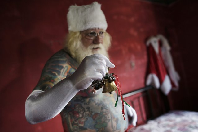 Vitor Martins holds a bell in front of his Santa Claus outfit inside his house, before a performance with children in Sao Caetano do Sul's town square, near Sao Paulo, December 7, 2014. (Photo by Nacho Doce/Reuters)