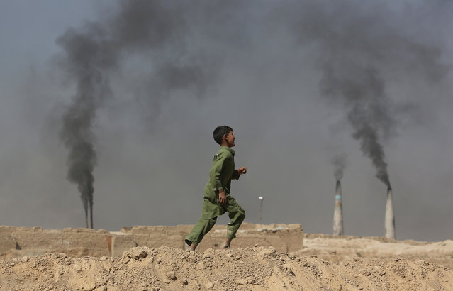 An Afghan boy runs past at a local brick factory on the outskirts of Kabul, Afghanistan, Monday, September 19, 2016. (Photo by Rahmat Gul/AP Photo)