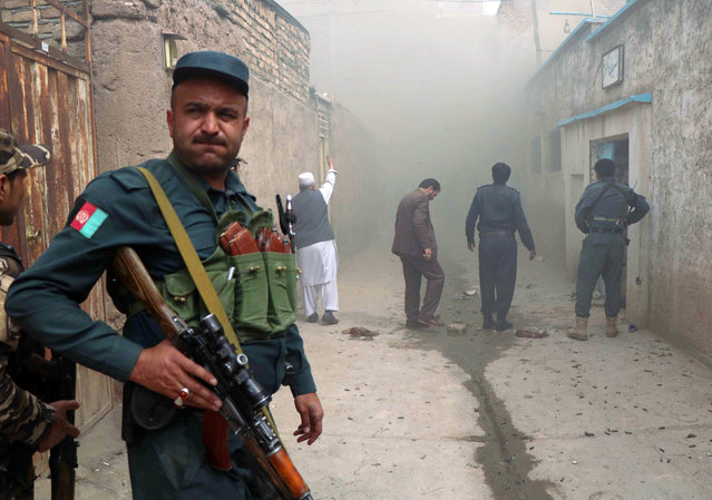An Afghan police officer stands guard outside a Shi'ite mosque after a suicide bomb attack in Herat, Afghanistan March 25, 2018. (Photo by Mohammad Shoib/Reuters)