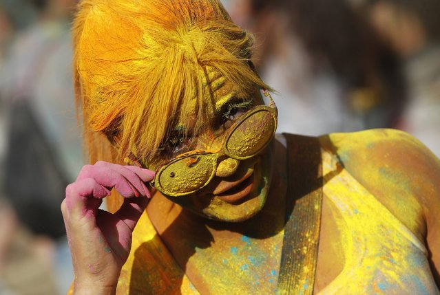 A woman, covered in coloured powder poses, during the Holi Festival of Colors, in Lisbon, Sunday, September 14 2014. The festival is fashioned after the Hindu spring festival Holi, which is mainly celebrated in some regions of India and Nepal. (Photo by Francisco Seco/AP Photo)