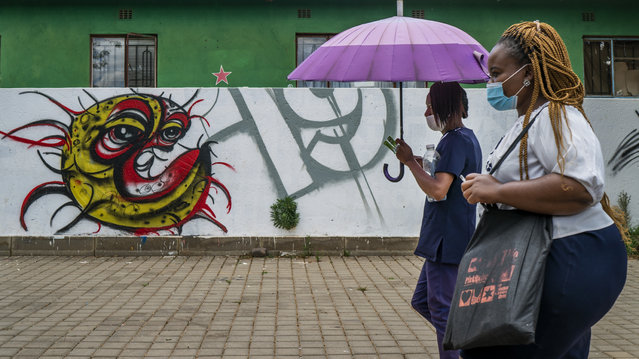 """Two women walk past a COVID-19 graffiti in Soweto's Orlando West township near Johannesburg, South Africa, Thursday November 19, 2020. Africa has surpassed 2 million confirmed coronavirus cases as the continent's top public health official warns that """"we are inevitably edging toward a second wave"""" of infections. The 54-nation continent of 1.3 billion people is being warned against """"prevention fatigue"""" as countries loosen pandemic restrictions to ease their economies' suffering and more people travel. (Photo by Jerome Delay/AP Photo)"""