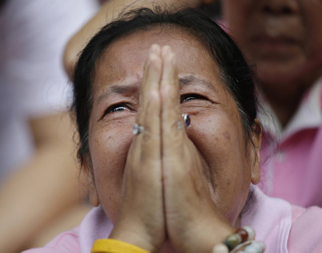 A woman prays for Thailand's King Bhumibol Adulyadej outside Siriraj Hospital where the king is being treated in Bangkok, Thailand, Thursday, October 13, 2016. The royal palace said in a statement late Wednesday that the 88-year-old king's blood pressure had dropped, his liver and kidneys were not working properly and he remained on a ventilator. (Photo by Sakchai Lalit/AP Photo)